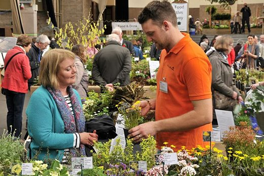 an exhibitor selling plants to a show visitor